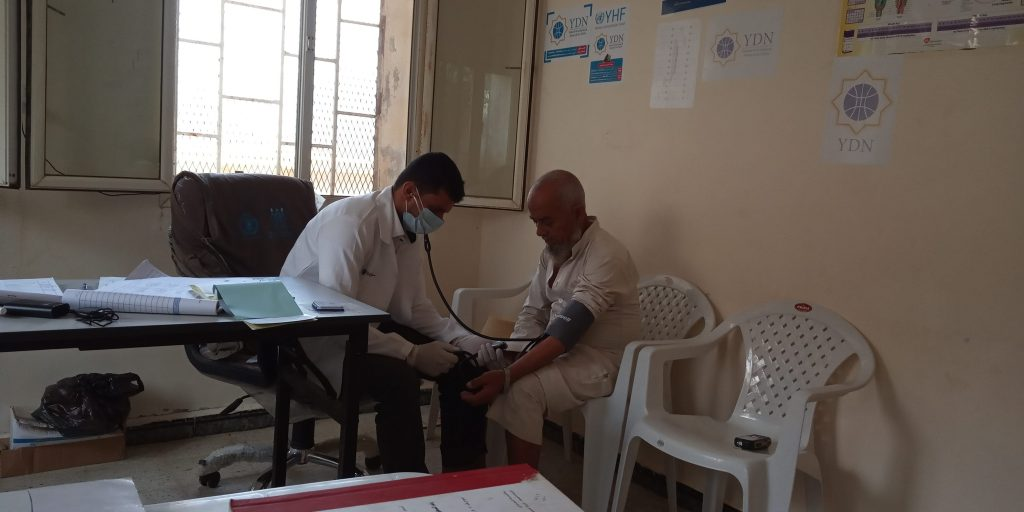 a patient man is getting his BP measured by the doctor after the unit regained functionality